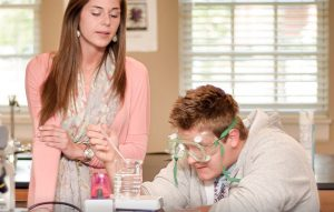 A chemistry student wears splash goggles next to a woman not wearing hers